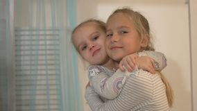 Two little girls smile and hug at home. Two beautiful little girls smile and hug at home stock video footage