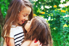 Two beautiful little girls smiling and playing at the garden Stock Image
