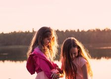 Two beautiful little girls smiling and playing at the seaside du Royalty Free Stock Images