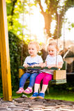Two beautiful little girls swinging in the park. Royalty Free Stock Photos