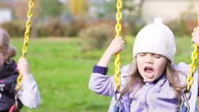 Two beautiful little girls on a swings outdoor in the playground stock video