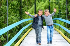 Two beautiful little guys running along the bridge in the Carpathians stock photo