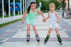 Two beautiful little sisters in a roller skates Royalty Free Stock Images