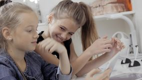 Two beautiful little sisters sit at a table and play on a Tablet PC. Happy smiling girls. Two beautiful little sisters sit at a table and play on a Tablet PC stock footage