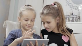 Two beautiful little sisters sit at a table and play on a Tablet PC. Happy smiling girls. Two beautiful little sisters sit at a table and play on a Tablet PC stock video