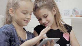 Two beautiful little sisters sit at a table and play on a Tablet PC. Happy smiling girls. Two beautiful little sisters sit at a table and play on a Tablet PC stock video footage
