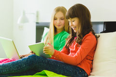 Two beautiful little sisters sitting on bed and play with a Tablet or laptop Royalty Free Stock Photography