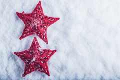 Two Beautiful magical vintage red stars on a white snow background. Winter and Christmas concept Royalty Free Stock Image