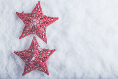 Two Beautiful magical vintage red stars on a white snow background. Winter and Christmas concept Stock Photography