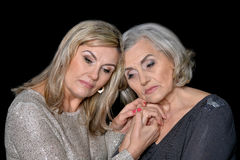 Two beautiful mature women. Portrait of two beautiful mature women against black royalty free stock image