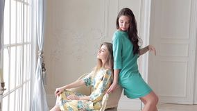 Two beautiful models in romantic dresses posing in studio sitting on chair. Backstage of photoshoot for lookbook spring-summer collection of dresses stock video
