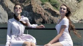 Two beautiful models in white light sundresses sitting on board of the boat stock video footage