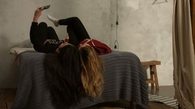 Cute girls lying on bed taking selfie upside down stock video