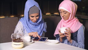Two beautiful muslim girl in cafe. Young girls in hijabs spend time together.  stock video
