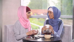 Two Beautiful Muslim Girls In Cafe. Muslim women talk in cafes and use mobile phones stock video