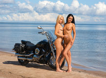 Two beautiful naked women with motorcycle Stock Images