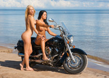 Two beautiful naked women with motorcycle Royalty Free Stock Image