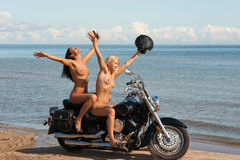 Two beautiful naked women with motorcycle Royalty Free Stock Photography