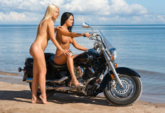 Two beautiful naked women with motorcycle Stock Image