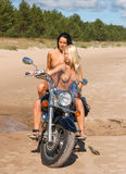 Two beautiful naked women with motorcycle Royalty Free Stock Images