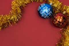 Two beautiful New Year`s toys red and blue with pattern with golden tinsel on red background. Copy space. stock images