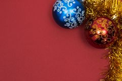Two beautiful New Year`s toys red and blue with pattern with golden tinsel on red background. Copy space. royalty free stock image