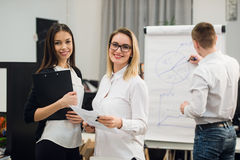 Two beautiful office workers having conversation while man colleague drawing business strategy on flip chart. Royalty Free Stock Image