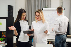 Two beautiful office workers having conversation while man colleague drawing business strategy on flip chart. Stock Image