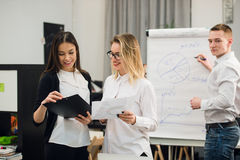 Two beautiful office workers having conversation while man colleague drawing business strategy on flip chart. Royalty Free Stock Photos