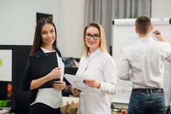 Two beautiful office workers having conversation while man colleague drawing business strategy on flip chart. Stock Photo