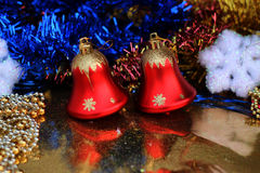 Two beautiful red bells on a brilliant background closeup with multicolored glittering garlands and snowflakes Stock Photos