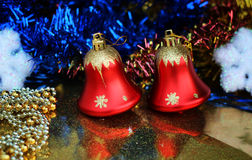 Two beautiful red bells on a brilliant background closeup with multicolored glittering garlands and snowflakes Royalty Free Stock Photos