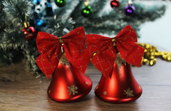Two beautiful red shiny bells closeup on the background of Christmas tree and tinsel on the wooden floor. Stock Image