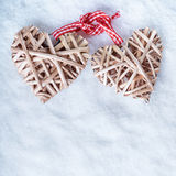 Two beautiful romantic vintage entwined beige flaxen hearts tied together with a ribbon on a white snow winter background. Stock Photography