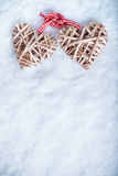 Two beautiful romantic vintage entwined beige flaxen hearts tied together with a ribbon on a white snow winter background. Royalty Free Stock Image