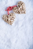 Two beautiful romantic vintage entwined beige flaxen hearts tied together with a ribbon on a white snow winter background. Royalty Free Stock Photos