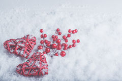 Two beautiful romantic vintage red hearts with mistletoe berries on white snow. Christmas, love and St. Valentines Day concept Royalty Free Stock Images