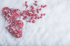 Two beautiful romantic vintage red hearts with mistletoe berries on white snow. Christmas, love and St. Valentines Day concept Stock Photos