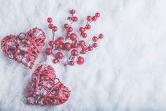Two beautiful romantic vintage red hearts with mistletoe berries on white snow. Christmas, love and St. Valentines Day concept Stock Photography