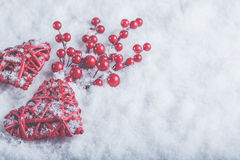 Two beautiful romantic vintage red hearts with mistletoe berries on white snow. Christmas, love and St. Valentines Day concept Royalty Free Stock Image