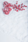 Two beautiful romantic vintage red hearts with mistletoe berries on white snow. Christmas, love and St. Valentines Day concept Stock Image