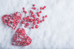 Two beautiful romantic vintage red hearts with mistletoe berries on white snow. Christmas, love and St. Valentines Day concept Royalty Free Stock Photography