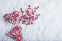 Two beautiful romantic vintage red hearts with mistletoe berries on white snow. Christmas, love and St. Valentines Day concept Stock Photo