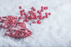 Two beautiful romantic vintage red hearts with mistletoe berries on white snow. Christmas, love and St. Valentines Day concept Stock Images