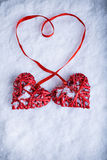 Two beautiful romantic vintage red hearts tied together with a ribbon on a white snow background. Love, St. Valentines Day concep Stock Images