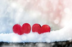 Two beautiful romantic vintage red hearts together on a white snow winter background. Love and St. Valentines Day concept.  royalty free stock photography