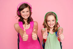Two beautiful schoolgirls giving thumbs up Stock Photos