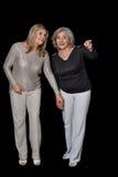 Two beautiful senior women. Posing against black background stock photography