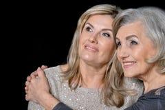 Two beautiful senior women. Posing against black background royalty free stock photos