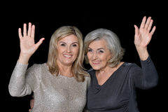 Two beautiful senior women. Posing against black background stock images